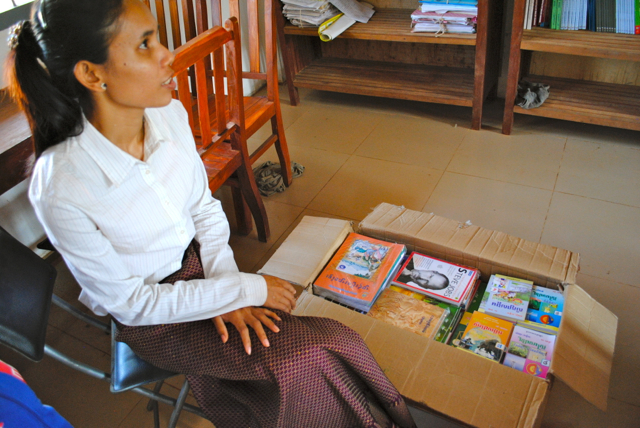 Our English/High Tech Teacher, Phala Ol with some of the books donated by WAWK Grant
